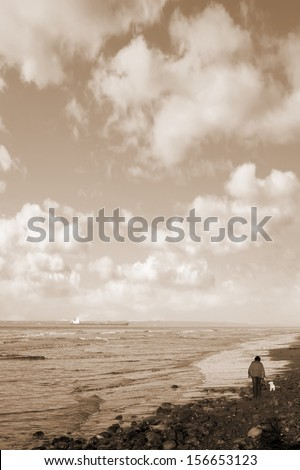 woman and her dog taking a walk along Beale beach in county Kerry Ireland in sepia
