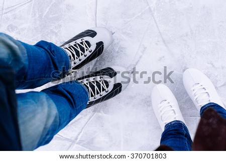 Woman and man  ice skating. winter outdoors on ice rink. ice and legs