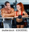 Woman and man to do exercises at the gym apparatus - stock photo