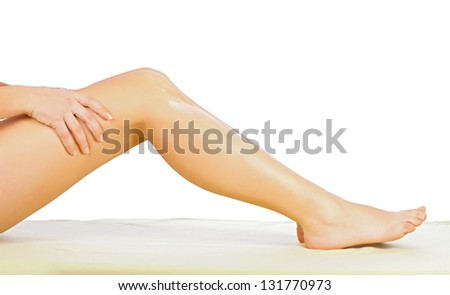 Woman applying body cream on her leg isolated on white.