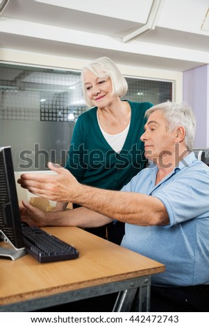 Woman Assisting Male Friend In Using Computer At Classroom