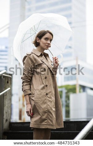 Woman at coat standing on stairs stages