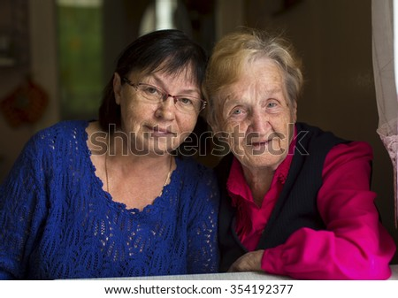Woman at the age with his old mother.