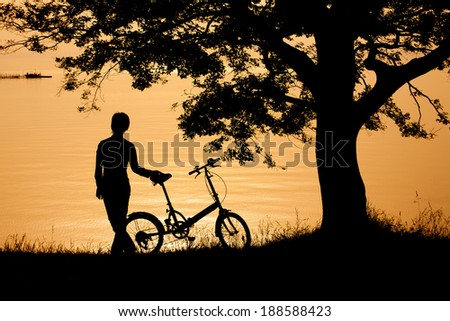 Woman at the lakeside with bike