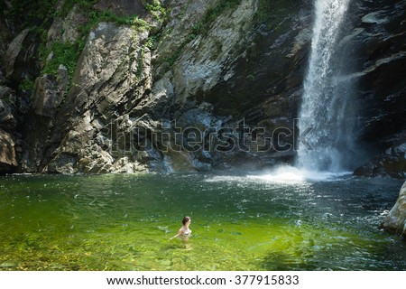 Woman bathing in clear waterfall lagoon in summer, Niigata, Japan