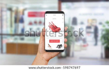 Woman buy red shoes online with mobile phone. E shopping with web site or app. Clothes and footwear shop in background.