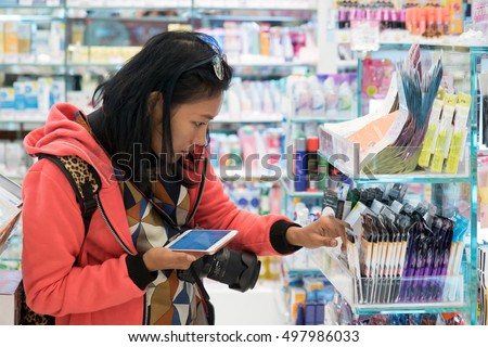Woman buys cosmetics in the store. Asian girl is looking at items in  shop. Consumers buy with help of smart-phone in hand. People choose cosmetics products with phone assistance. Check price at shop.