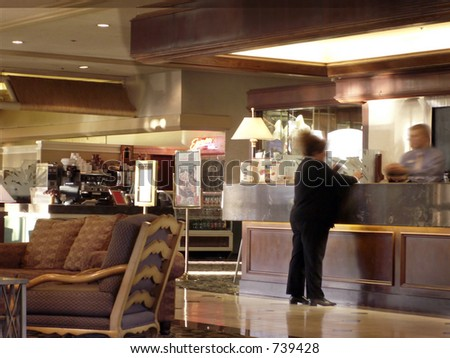 Woman checks in at hotel desk with desk clerk -- coffee bar at back.