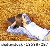 Woman chilling in wheat golden field on old retro suitcase - stock photo