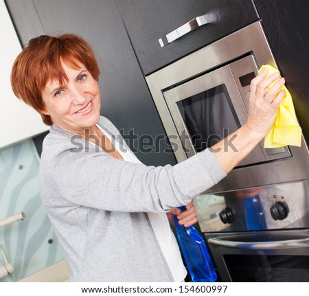 Woman cleaning the kitchen. Adult woman washing microwave