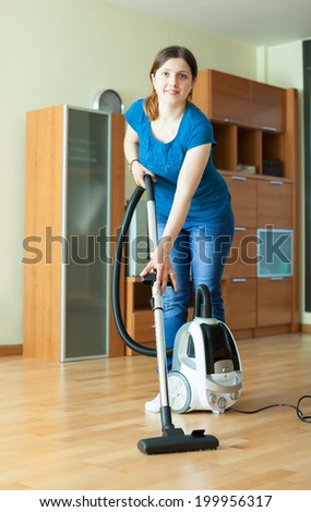 Woman cleans with vacuum cleaner on parquet floor