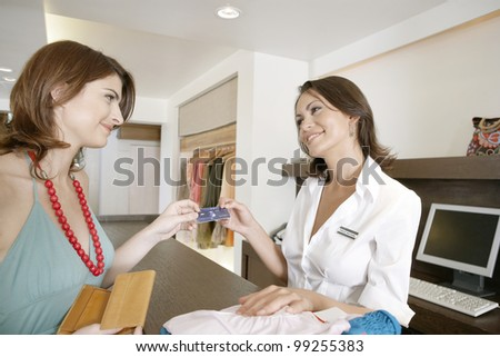 Woman client handing over her credit card at the till, making a purchase.