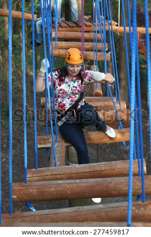 Woman climber sitting on a log in the adventure park