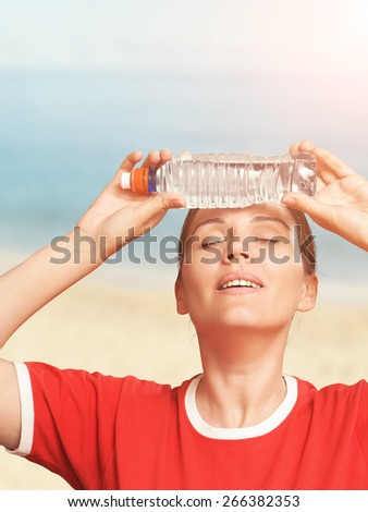 Woman cooling herself with water bottle. Heat.