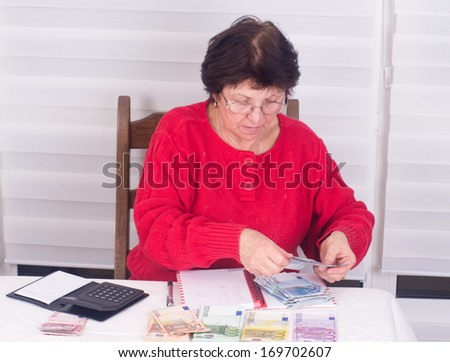 Woman counting money on table with calculator and notebook