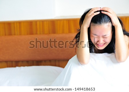 woman crying sitting on the bed clawing her head in sad