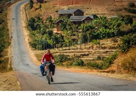Woman cycling solo through beautiful Madagascar countryside