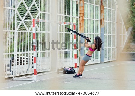 Woman doing arms biceps curl training with trx fitness straps. Healthy outdoor fitness workout for strength and loosing weight.