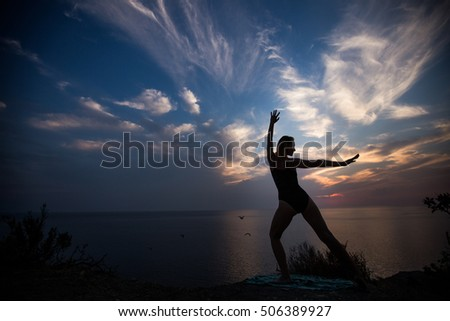 Woman doing exercise on a background of a beautiful sunset.