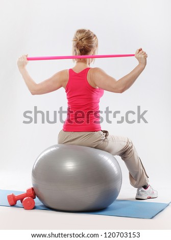 Woman doing exercise with tape view from the back over a grey background