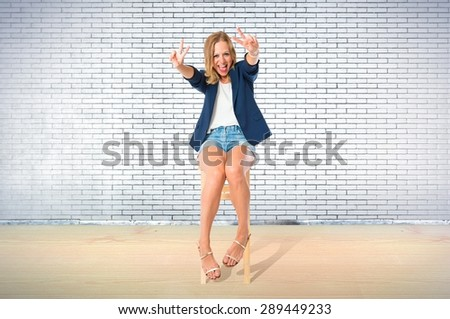 Woman doing victory gesture over textured background