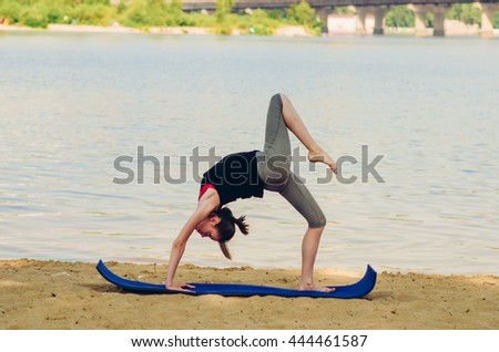 Woman doing yoga in the morning at the beach.