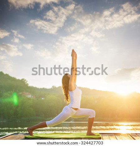 Woman doing yoga on the lake - beautiful lights