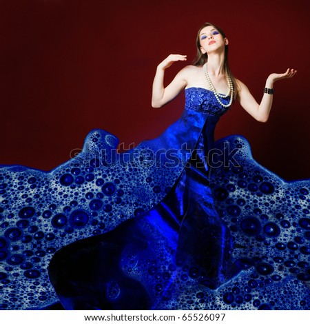 Woman dressed in blue soap bubble evening garment, grain added