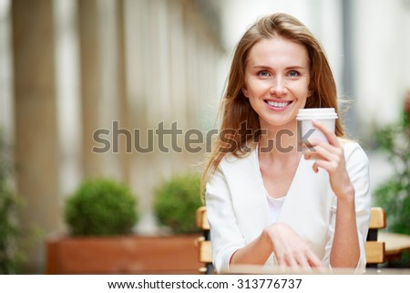 Woman drinking coffee at street cafe. Natural light