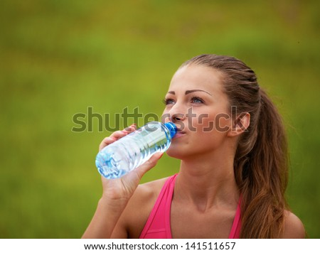 Woman drinking water from a bottle in nature