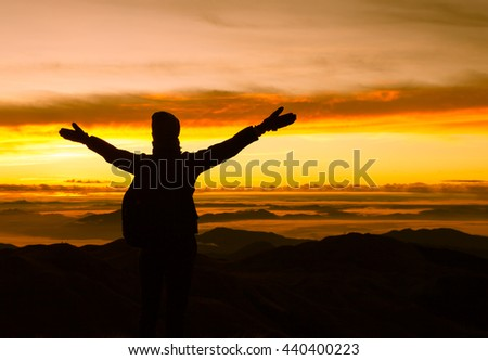 Woman enjoying beautiful sunrise on the top of mountain