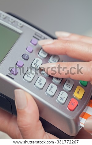 woman entering pin number to pos terminal. Paying with credit card concept.