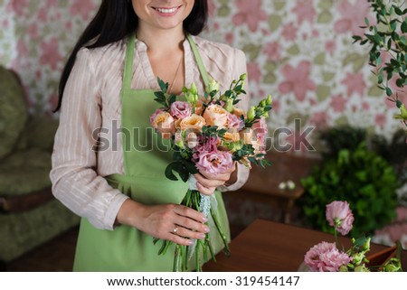 Woman florist holding a bouquet of roses to a wedding
