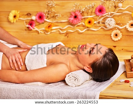 Woman getting  massage in wooden spa.