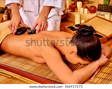 Woman getting stone therapy massage on bamboo floor spa.