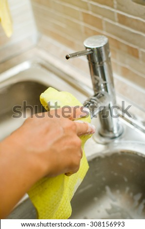 Woman hand doing chores in the kitchen at home , cleaning sink and faucet with a yellow sponge