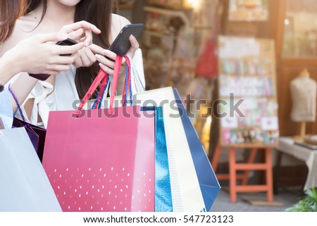 Woman hand  shopping  using smartphone with shopping bag
