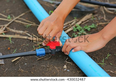 Woman hand twist Red Water valve for open water used in agriculture