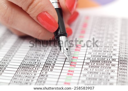woman hand with ink pen calculate income