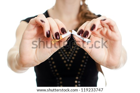 Woman hands breaking the cigarette. Isolated on white.