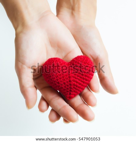 Woman hands holding red crocheted heart. Valentine's Day. Symbol of love.