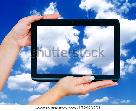 woman hands holding tablet with blue sky with white clouds on the screen