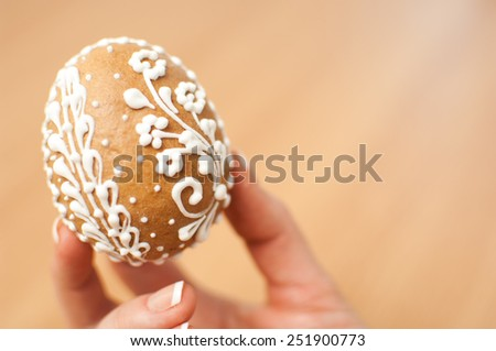 Woman hands holding traditional easter eggs with handmade patterns.