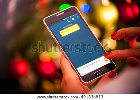 Woman hands holds touchscreen mobile phone and sending Merry Christmas message on Christmas eve in the front of the christmas tree colorful lights
