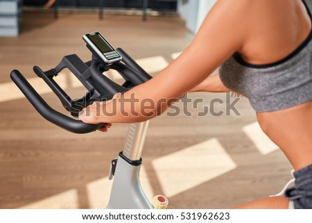Woman hands on a bar stationary bike  the gym