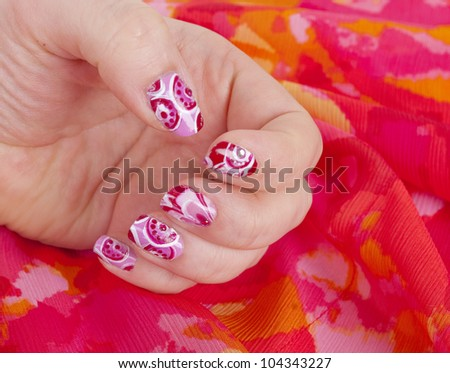 Woman  hands with art modern pink abstract manicure on the bright background.