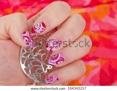 Woman  hands with art modern pink abstract manicure with  silver pedant on the bright background.