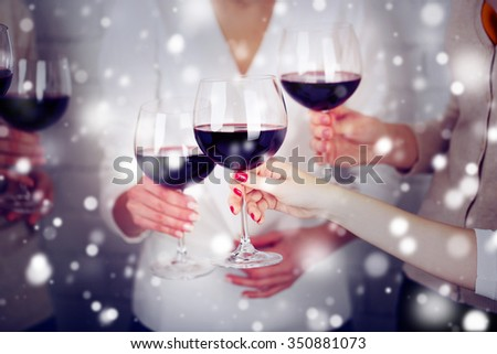 Woman hands with glasses of wine over snow effect