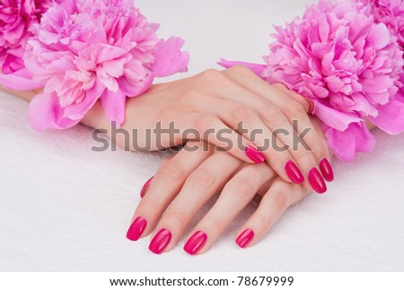 Woman hands with pink manicure lying down with flowers
