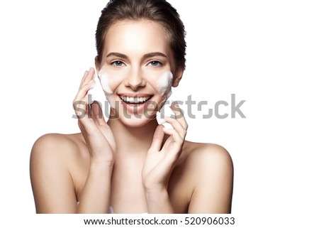Woman happy cleanses  the skin foam on a white background isolated